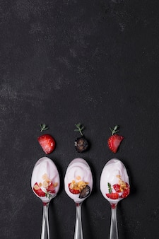 Top view selection of spoons with yogurt and fruits