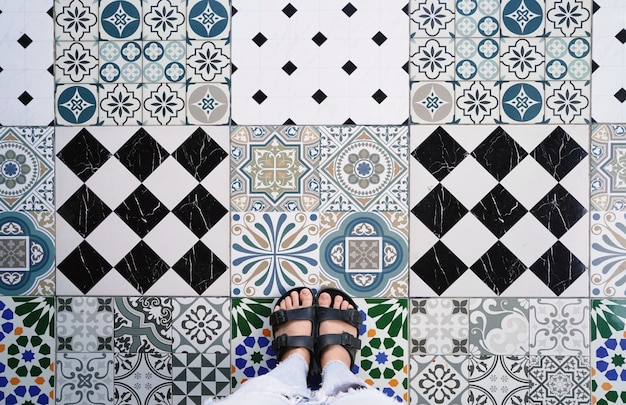 Top view selfie of feet in sandals shoes on the various vintage tiles