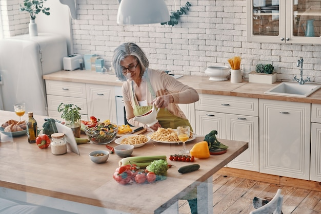Top view of senior woman in apron cooking healthy dinner while spending time at home