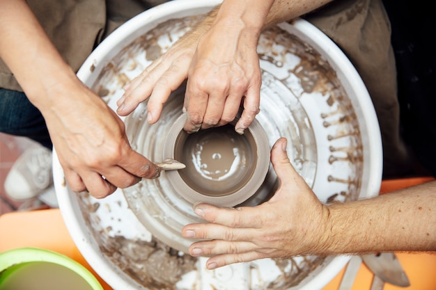Top view at senior woman spinning clay on a wheel with teacher at pottery class