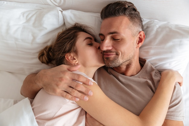 Top view of sensual loving couple lying together in bed at home while woman kissing her boyfriend