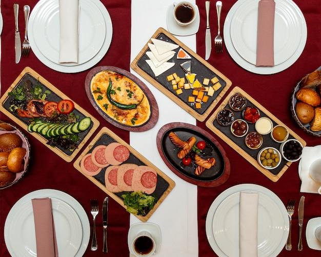Вид сверху подается стол с завтраком на столе сыр колбаски яичница варенье и хлеб