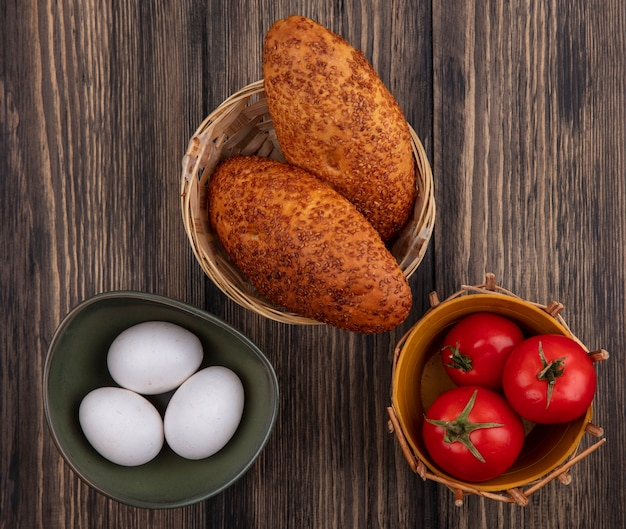 Top view of sesame patties on a bucket with organic eggs on a bowl and fresh tomatoes on a bucket on a wooden background