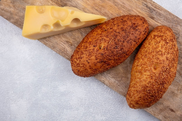 Vista dall'alto di tortini di sesamo su una tavola di cucina in legno con formaggio su uno sfondo bianco