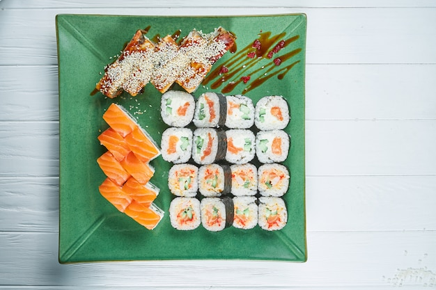 Top view on set of assorted roll and sushi on green plate isolated on white wooden background. sushi with salmon, eel. japanese sushi food