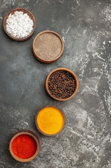 Top view of set of different spices in brown bowls on gray background
