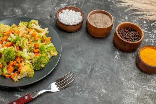 Vista dall'alto del set di diverse spezie in ciotole marroni e insalata di verdure e forchetta sul tavolo grigio