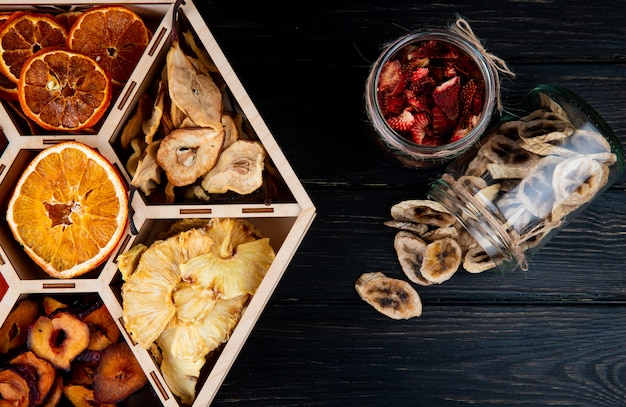 Top view of a set of dried fruits in a wooden box and dried banana and strawberry chips in glass jars on black background