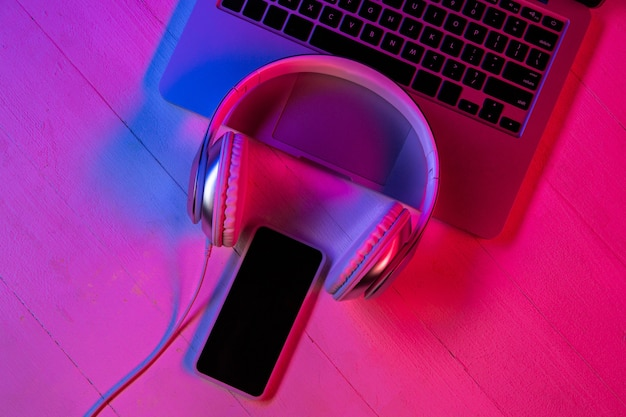 Top view of set of gadgets in purple neon light and pink background. laptop keyboard, headphones and smartphone with black screen. copyspace for your advertising. tech, modern, gadgets.