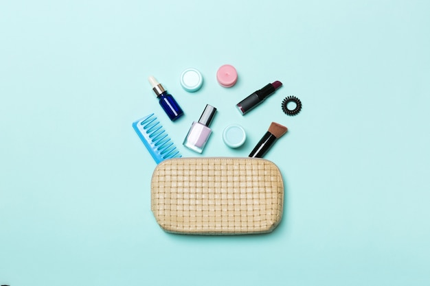 Top view of set of make up and skin care products spilling out of cosmetics bag on blue background. beauty concept.