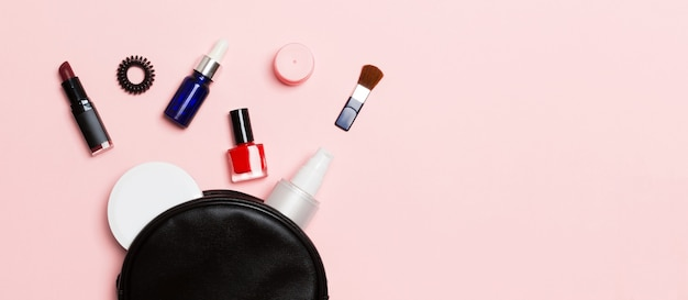 Top view of set of make up and skin care products spilling out of cosmetics bag on pink