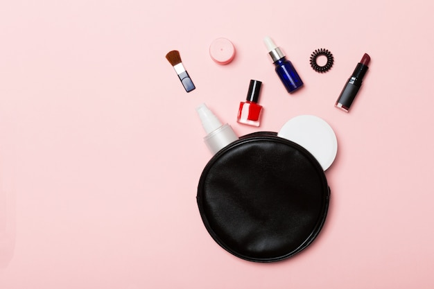 Top view of set of make up and skin care products spilling out of cosmetics bag