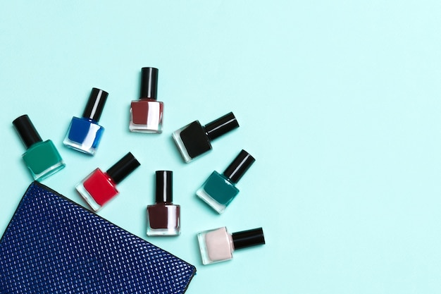 Top view of the set of nail polishes and bright gel varnishes fallen out of cosmetics bag with copy space on blue surface