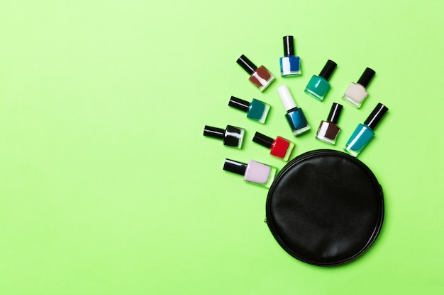 Top view of the set of nail polishes and bright gel varnishes fallen out of cosmetics bag with copy space on green background.