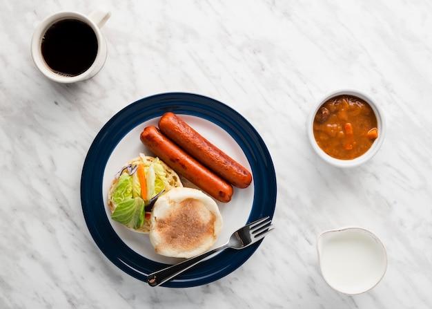 ソーセージの横にある朝食サンドイッチのトップビューセット