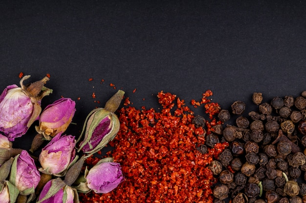 Top view of a set of spices and herbs tea rose buds red chili pepper flakes and black peppercorns on black background