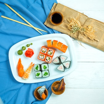 Top view of set of sushi and maki with soy sauce on blue and white