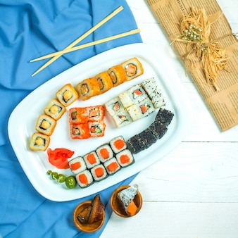 Top view of set of sushi with soy sauce on blue and white