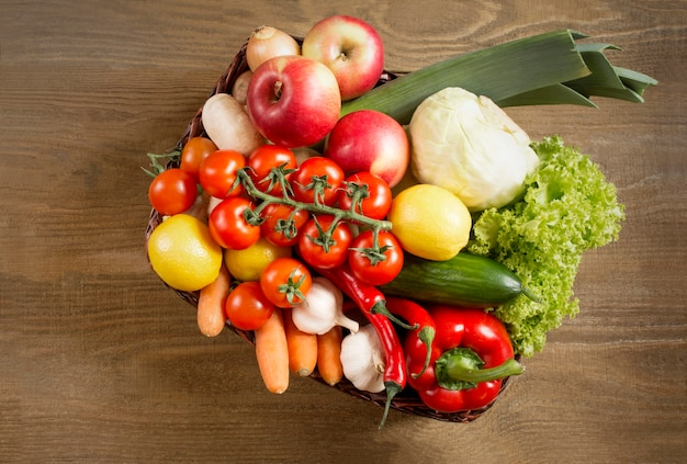 Top view of a set of vegetables and fruits in a wicker basket on a wooden background