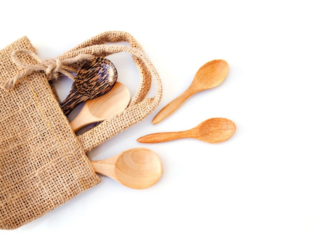 Top view set of wooden spoon in sack bag, natural materials for health isolated on white surface.