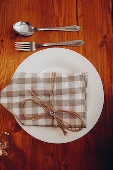 Top view of setting of white ceramic plate with checked brown and white napkin tied with rustic ribbon. served on brown wooden table.