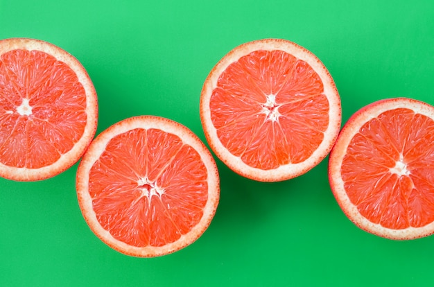 Top view of a several grapefruit slices on bright background in green color