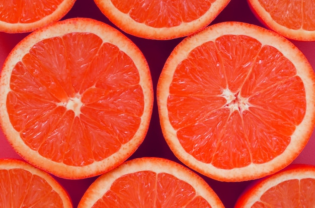 Top view of a several grapefruit slices on bright background in pink color.