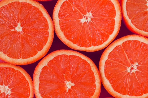 Top view of a several grapefruit slices on bright background in pink color
