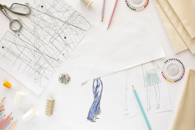 Top view of sewing essentials with textiles and drawing