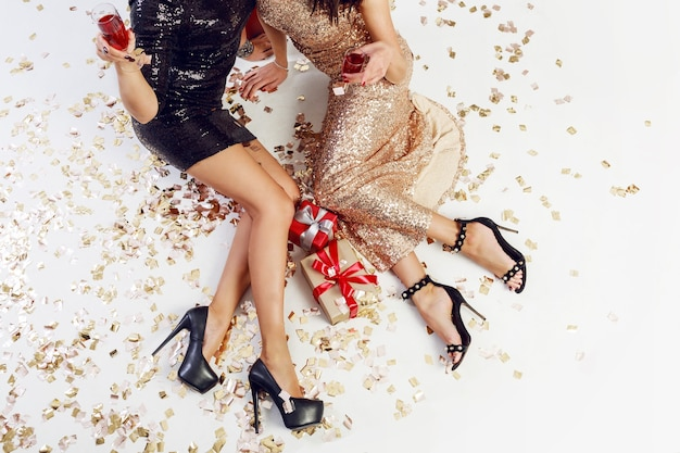 Top view on sexy women legs on background of shining golden confetti, gift boxes, glasses of champagne.  wearing  sparkly  evening  dress. celebrating time.