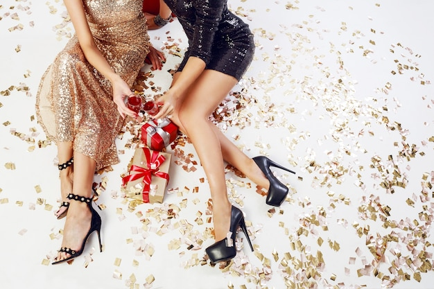 Top view on sexy women legs on background of shining golden confetti, gift boxes, glasses of champagne