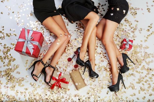 Vista dall'alto sulle gambe di donne sexy su sfondo di coriandoli dorati brillanti, scatole regalo, bicchieri di champagne