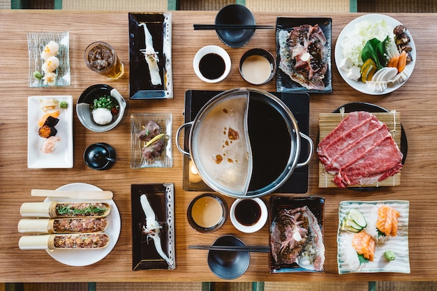 Top view of shabu set including rare slices wagyu a5 beef, shabu base, salmon, sushi and vegetables