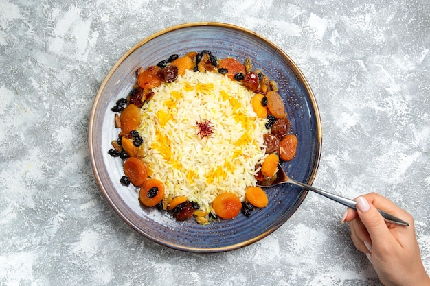 Top view shakh plov cooked rice dish with raisins inside plate on a white space