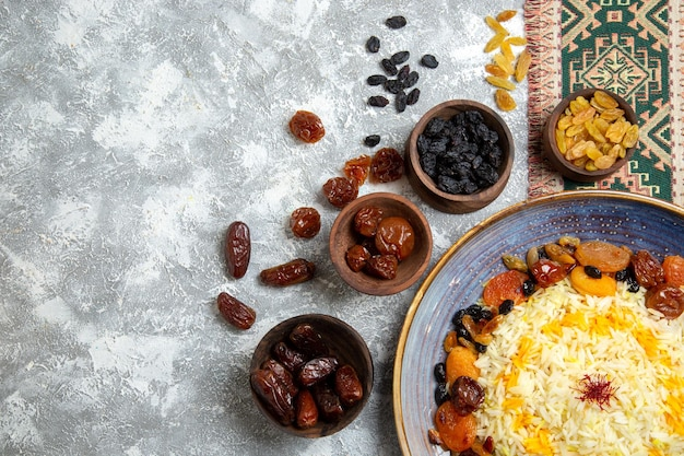 Top view shakh plov cooked rice dish with raisins inside plate on white space