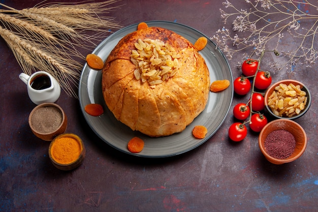 Top view shakh plov delicious eastern meal consists of cooked rice inside round dough on a dark surface cuisine rice food dough