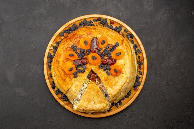 Top view of shakh plov delicious rice meal cooked inside round dough with raisins on dark grey surface