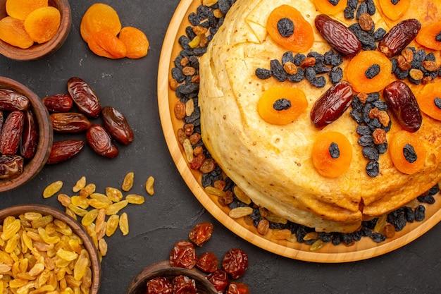 Vista dall'alto del delizioso pasto di riso shakh plov cucinato all'interno di un impasto rotondo con uvetta sulla superficie grigia