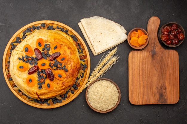 Top view of shakh plov delicious rice meal cooked inside round dough with raisins on a grey surface