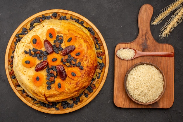 Top view of shakh plov delicious rice meal cooked inside round dough with raisins on grey surface
