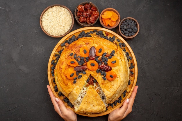 Top view of shakh plov delicious rice meal cooked inside round dough with raisins on the grey surface
