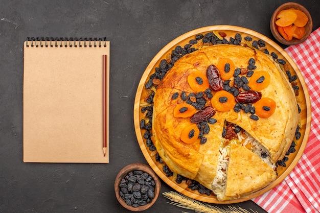Vista dall'alto di shakh plov delizioso pasto di riso cucinato all'interno di pasta rotonda con uvetta e blocco note sulla superficie grigia