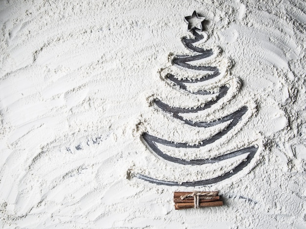 Top of view shaped christmas tree of flour star and cinnamon.