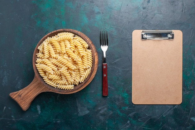 Top view shaped italian pasta delicious looking little pasta on the dark-blue desk