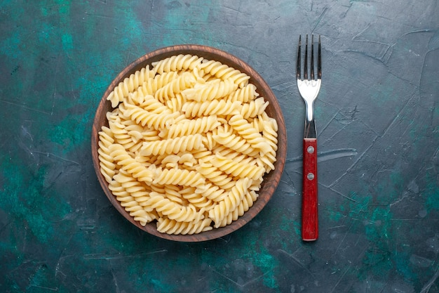 진한 파란색 책상에 갈색 냄비 안에 맛있는 이탈리아 파스타 모양의 상위 뷰 모양의 작은 파스타