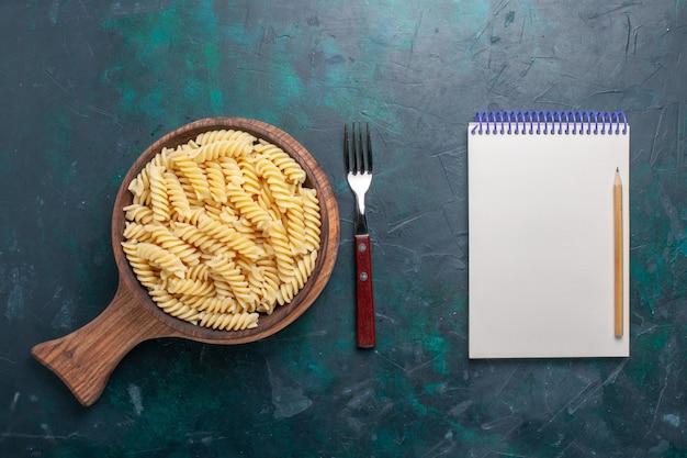 어두운 파란색 책상에 상위 뷰 모양의 이탈리아 파스타 맛있는 찾고 작은 파스타