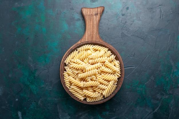 トップビューの形をしたイタリアンパスタダークブルーの机の上にある美味しそうな小さなパスタ