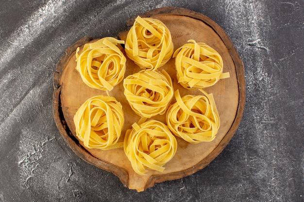 Vista dall'alto a forma di pasta italiana a forma di fiore crudo e giallo sullo scrittorio di legno marrone spaghetti italiani del pasto dell'alimento di colore crudo