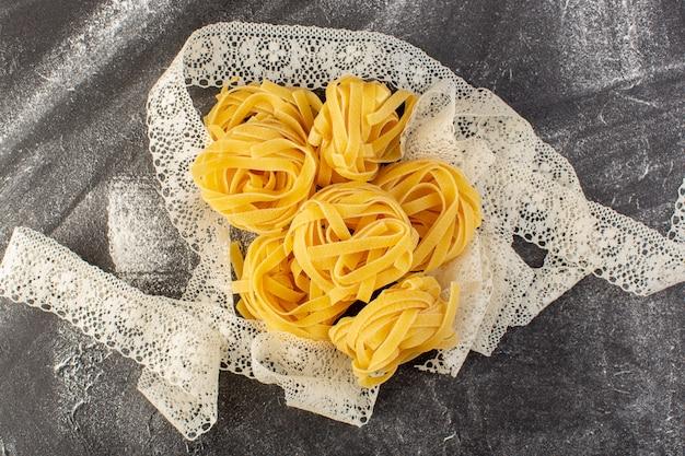 Vista dall'alto a forma di pasta italiana a forma di fiore crudo e giallo sulla scrivania grigia spaghetti crudi italiani