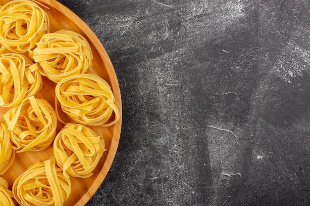 Vista dall'alto a forma di pasta italiana a forma di fiore crudo e giallo sulla scrivania in legno cibo italiano spaghetti pasto